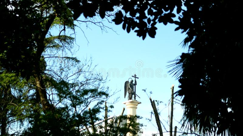 Statue brouill?e de silhouette d'un ange avec une ?p?e contre le ciel bleu dans le cadre du feuillage photos libres de droits
