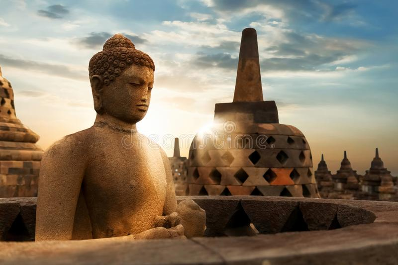 Statue of Buddha against the background of the sunrise in the temple of Borobudur. Java island. Indonesia. royalty free stock photo