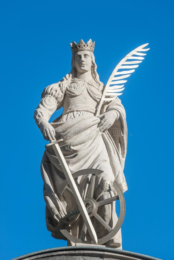 Statue of Catherin with writing bird feather, sword and cartwheel at ancient portal in Magdeburg, Germany, closeup, blue sky royalty free stock photo