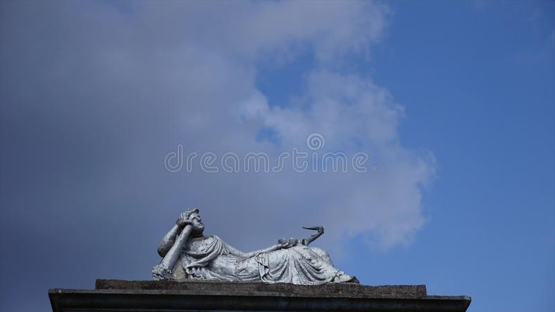 Statue in a cemetery with clouds. time lipse stock photo