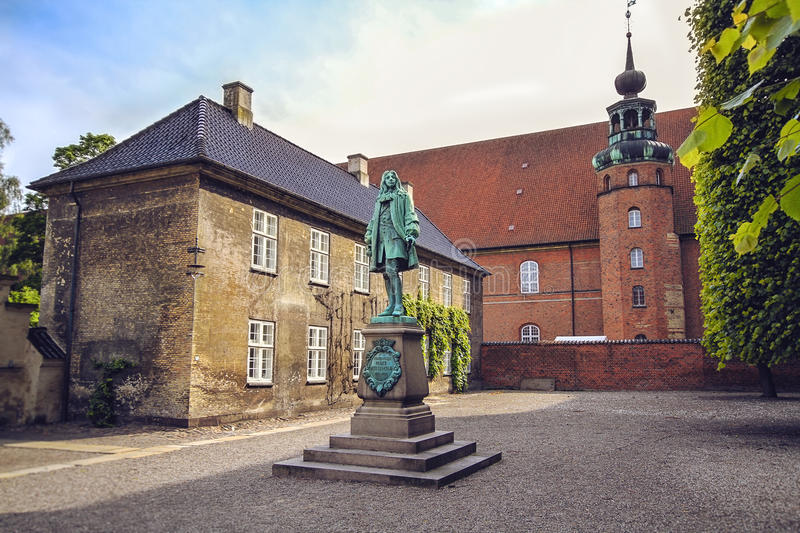 The statue of Chancellor Peder Griffenfeld and a tower in Copenhagen. The statue of Danish politician Chancellor Peder Griffenfeld and Tower in Royal Library in royalty free stock photo