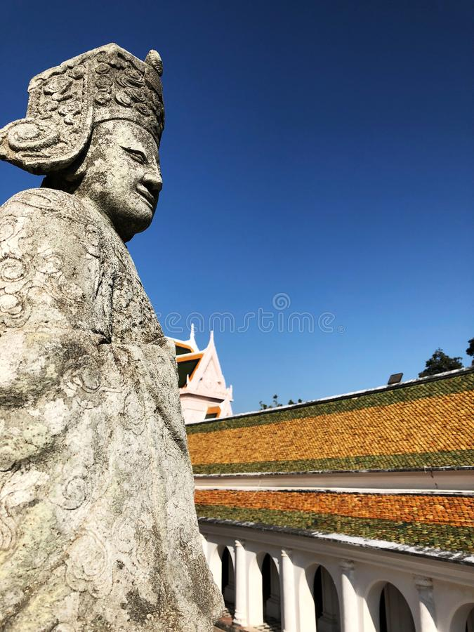 Statue of Chinese people in Thai temple with Roof. And clear blue sky background. Relationship . Copy space stock photography