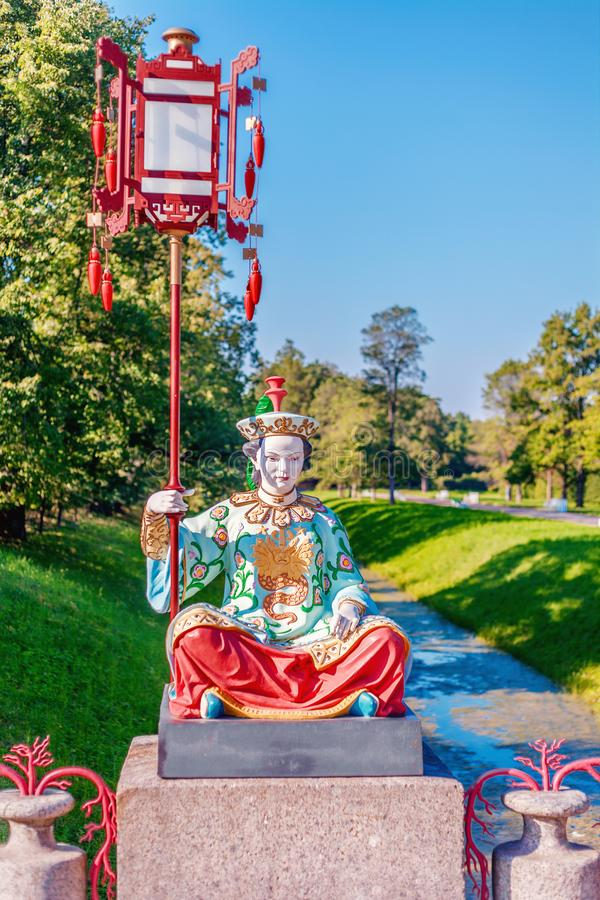 Statue of the Chinese woman sitting on a pedestal with a big lamp on a pole. Russia, Saint-Petersburg, Tsarskoye Selo stock image