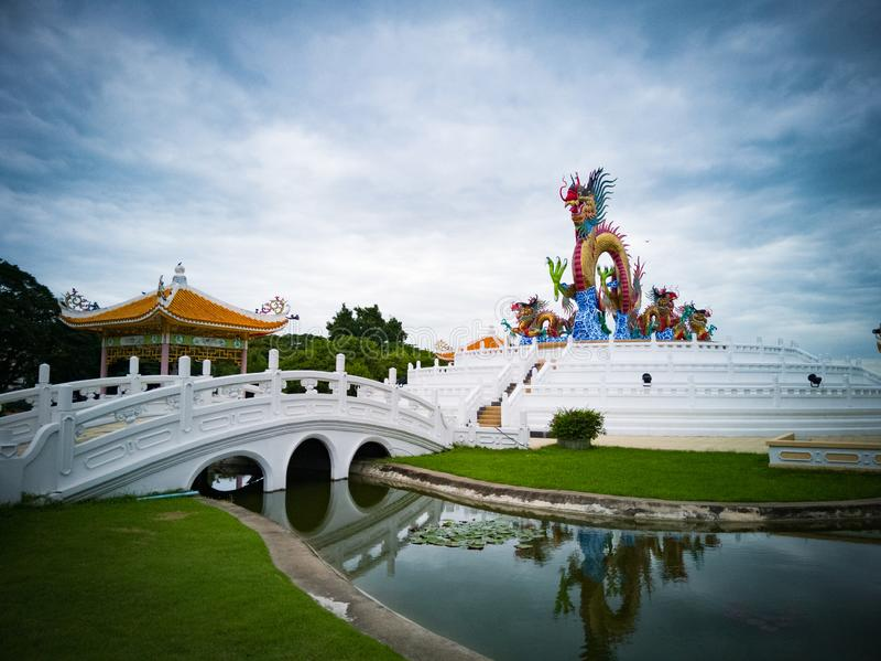 Statue chinoise de dragon avec le pont et l'étang Fond de ciel bleu photo libre de droits