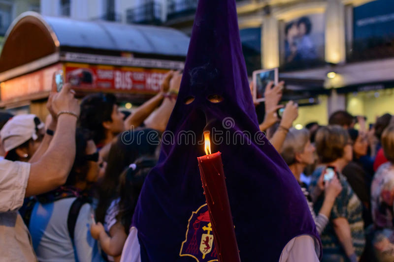 The statue of Christ leaving the church. A close up of a fraternity member wearing a purple hood and holding a lit candle during the procession of Nuestro Padre royalty free stock image
