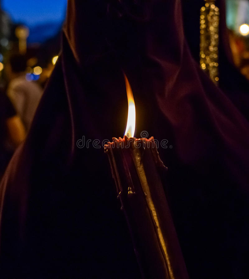 The statue of Christ leaving the church. A close up of a fraternity member wearing a purple hood and holding a lit candle during the procession of Nuestro Padre stock images
