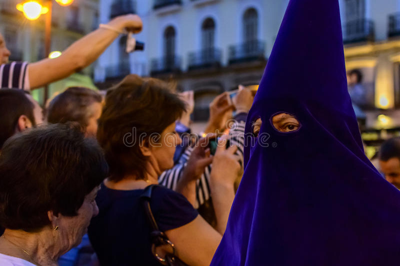 The statue of Christ leaving the church. A close up of a fraternity member wearing a purple hood during the procession of Nuestro Padre Jesús De La Salud Los stock photography