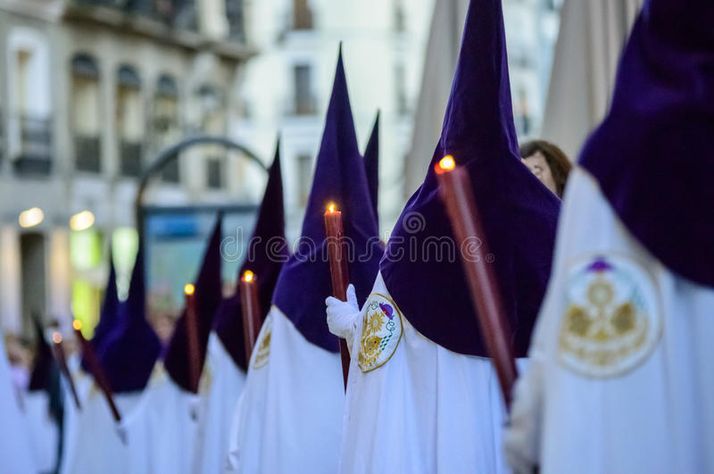 The statue of Christ leaving the church. A line up of members of the fraternity wearing white tunic and purple pointed hoods during the procession of Nuestro royalty free stock photography