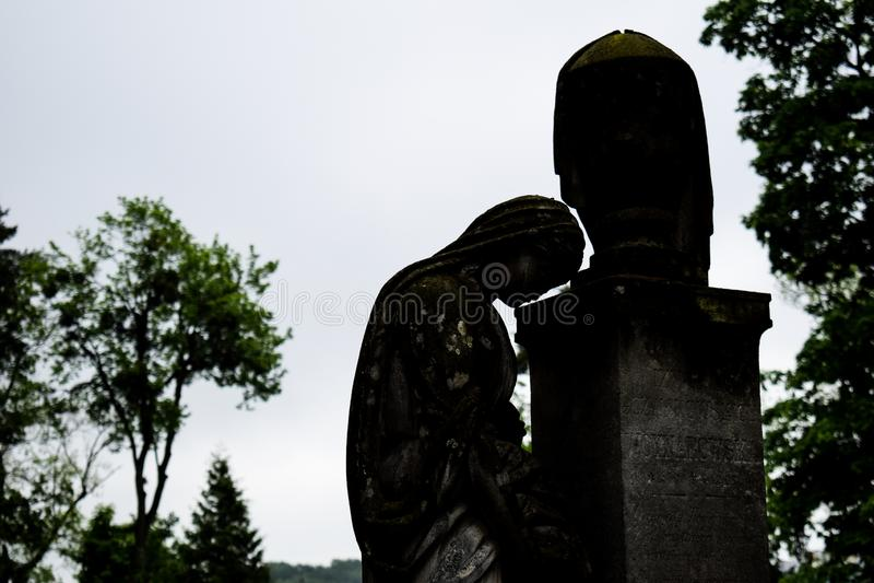 Statue commémorative de vieille pierre tombale dans le cimetière antique belle statue triste de fille dans le vieux cimetière de  photo libre de droits