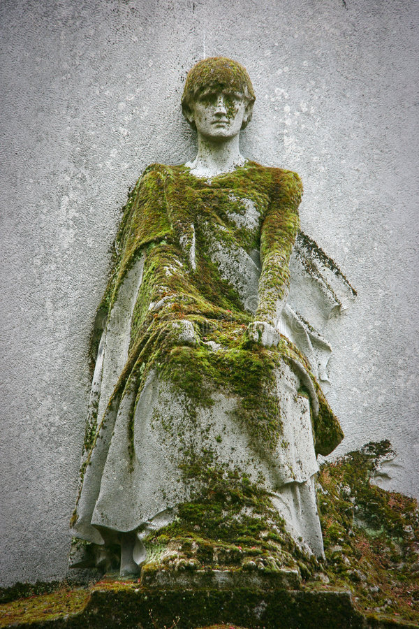 Statue covered with moss stock image