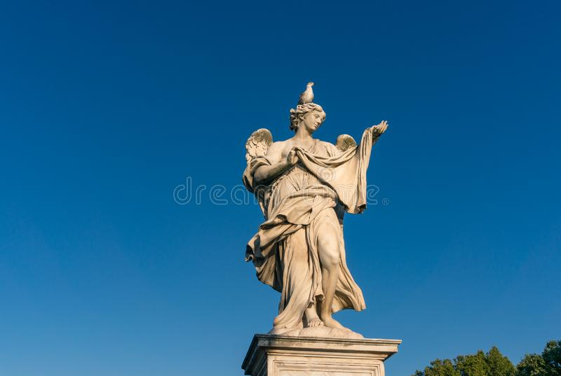 Statue d'ange avec l'oiseau se reposant sur sa tête image stock