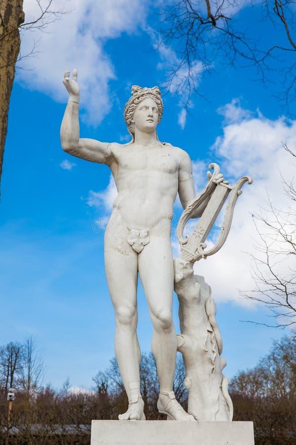 Statue d'Apollo avec une lyre au jardin du palais de Versailles dans un jour d'hiver de congélation juste avant le ressort images stock