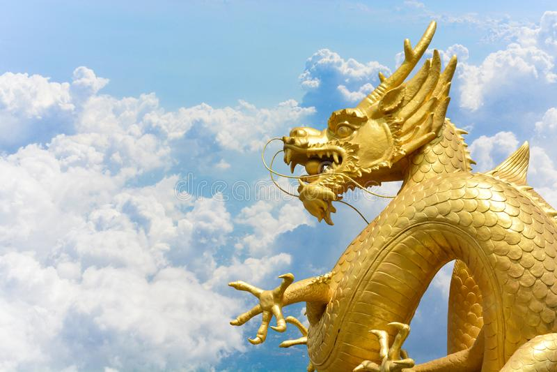 Statue d'or chinoise de dragon sur les nuages et le fond de ciel bleu images libres de droits