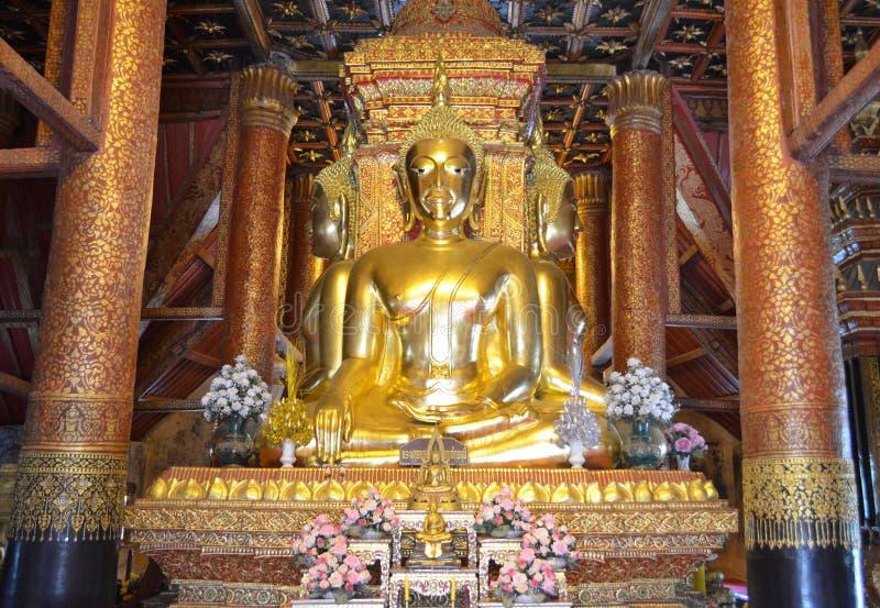 Statue d'or de Bouddha dans l'attitude de soumettre Mara au temple de Wat Phumin Phumin, province de Nan, Thaïlande photos libres de droits