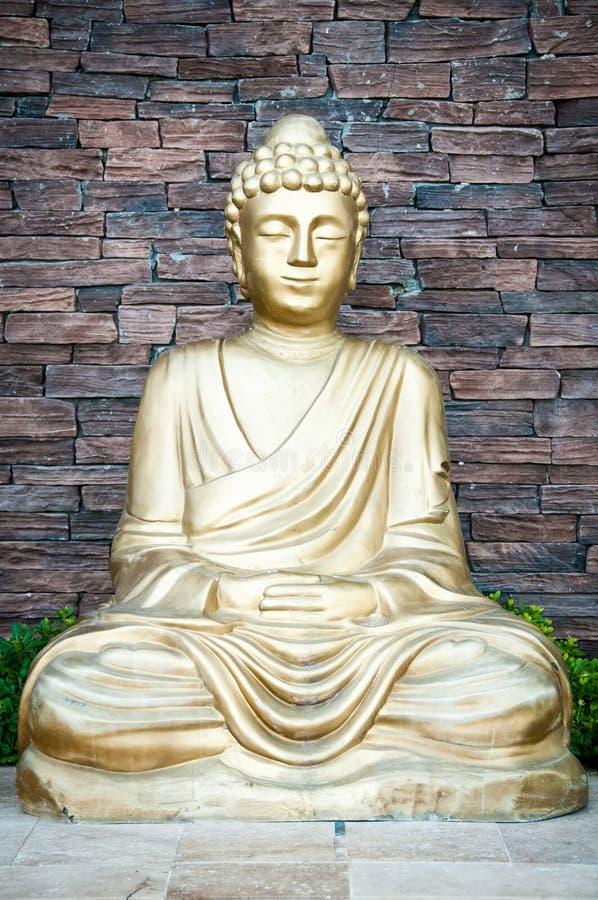 Statue d'or de Bouddha sur un fond de mur de briques image libre de droits