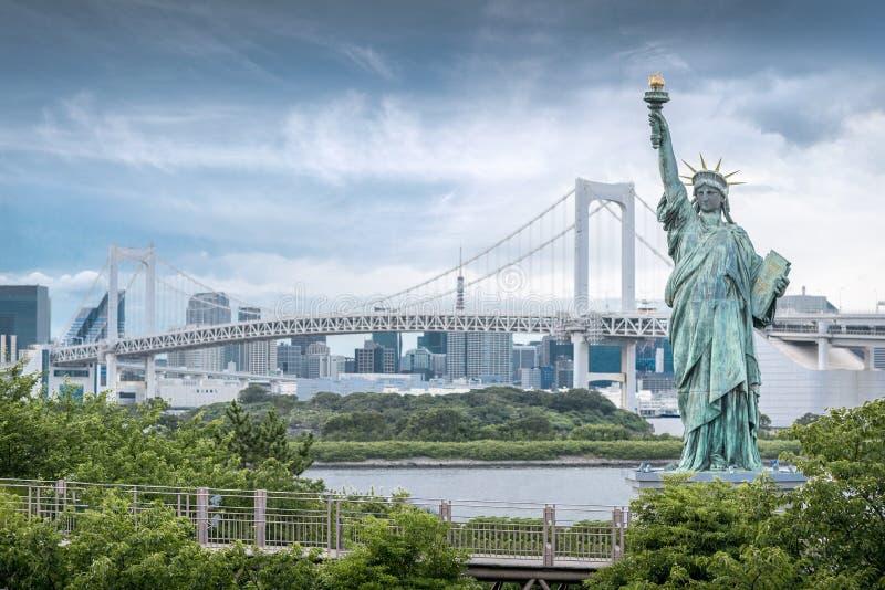 Statue d'Odaiba de la liberté avec le pont en arc-en-ciel et le fond de gratte-ciel photos libres de droits
