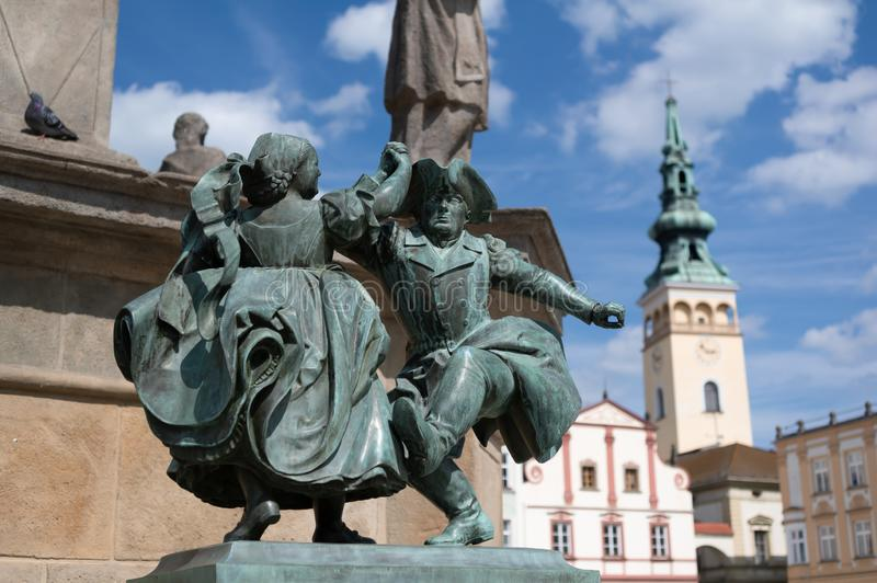 Statue of dancers, Novy Jicin, Czech Republic. / Czechia - small bronze monument and town hall in the background royalty free stock images