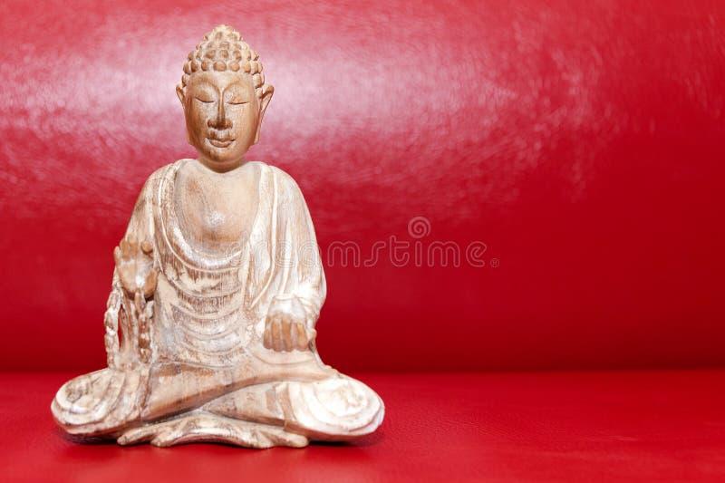 Statue de Bouddha en bois, symbole du bouddhisme sur fond rouge Espace libre pour le texte image stock