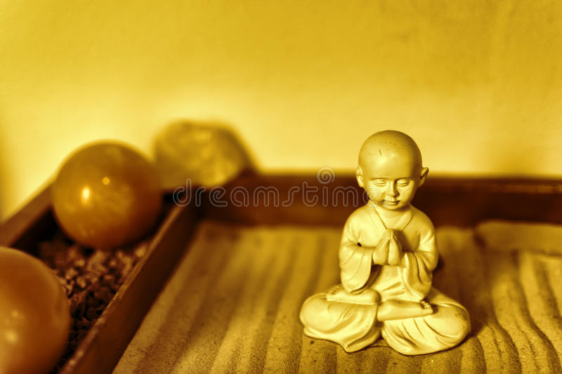 Statue de Bouddha en Lotus Position Sitting sur le sable Bouddha en Zen Garden With Smooth Lines en sable image libre de droits