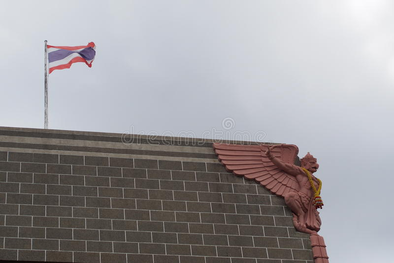 Statue de Garuda sur le vieux bâtiment Le drapeau thaïlandais est le contexte image stock