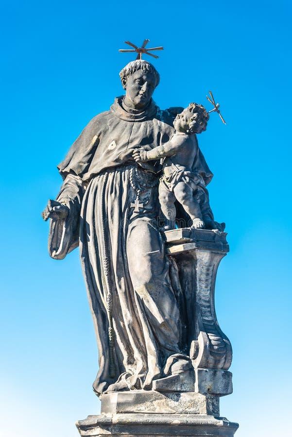 Statue de gros et grand prêtre avec un enfant chez Charles Bridge à Prague au ciel bleu, République Tchèque, heure d'été image libre de droits