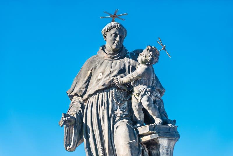 Statue de gros et grand prêtre avec un enfant chez Charles Bridge à Prague au ciel bleu, République Tchèque, heure d'été image stock