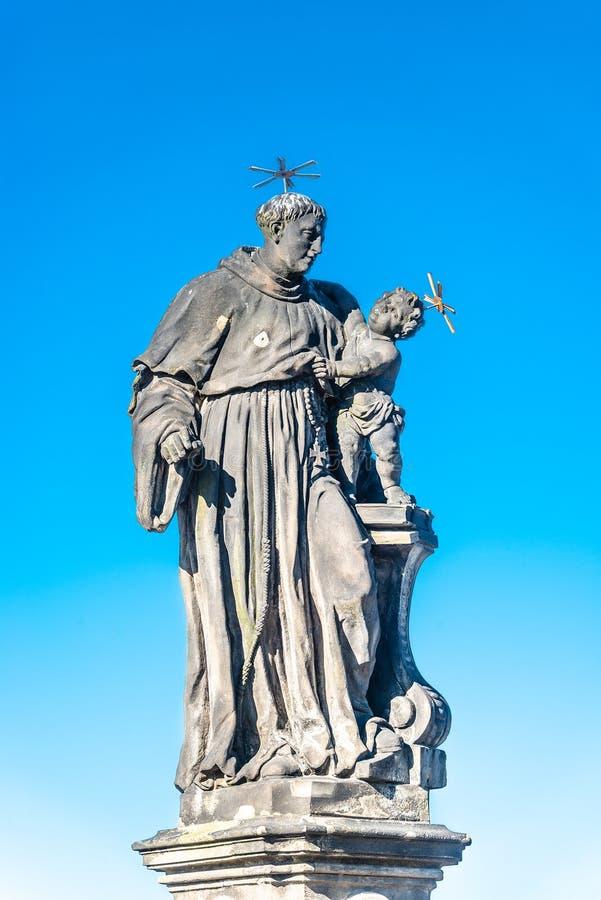 Statue de gros et grand prêtre avec un enfant chez Charles Bridge à Prague au ciel bleu, République Tchèque, heure d'été photographie stock libre de droits