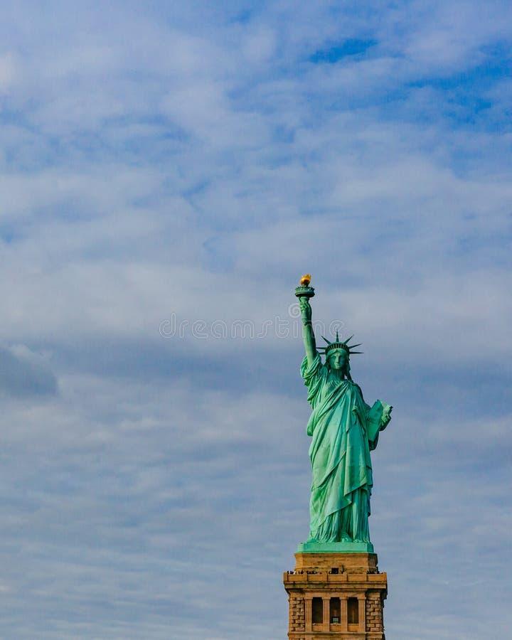Statue de la liberté contre le ciel et les nuages, à New York City, les Etats-Unis image libre de droits