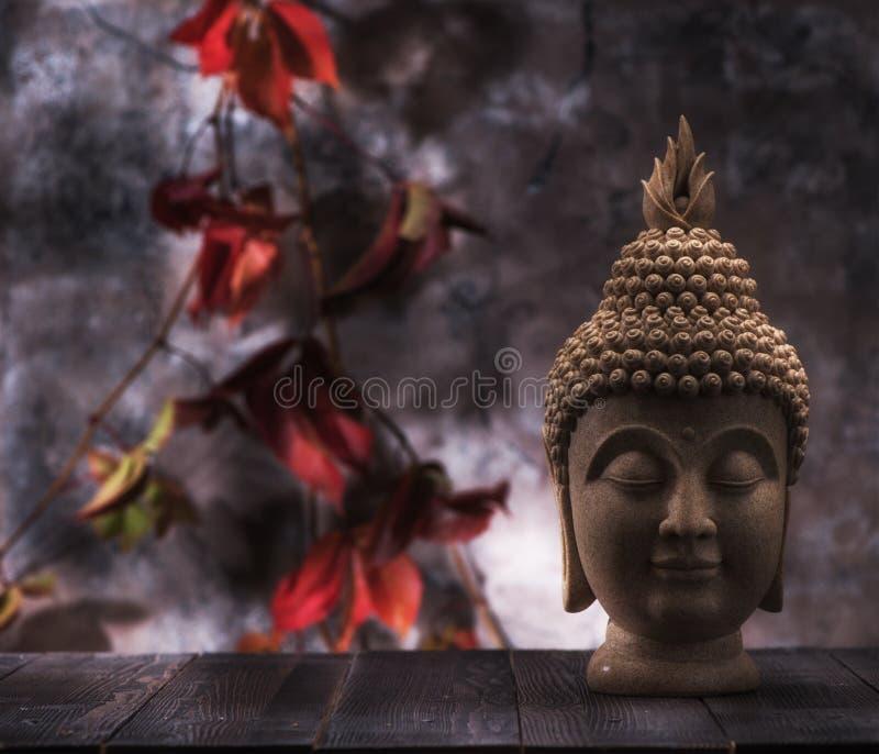 Statue de la tête de Bouddha sur fond de feuilles rouges photographie stock libre de droits
