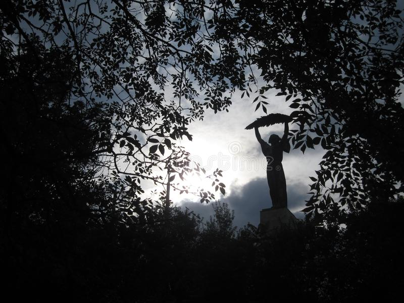 Statue de Madame tenant une feuille parmi les feuilles image stock