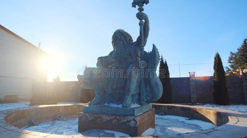 Statue de Neptune dans la fontaine tenant un trident dans la main gauche et le coquillage dans autre contre le ciel bleu en hiver photographie stock libre de droits