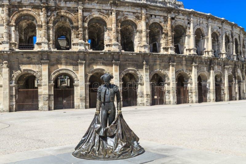 Statue de Nimeño II et amphithéâtre romain à Nîmes photo stock