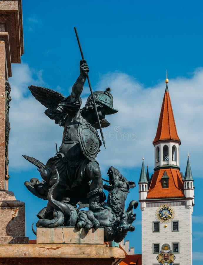 Statue de putto tuant un dragon sur le piédestal marial du ` s de colonne, Marienplatz avec Spielzeugmuseum à l'arrière-plan photos libres de droits