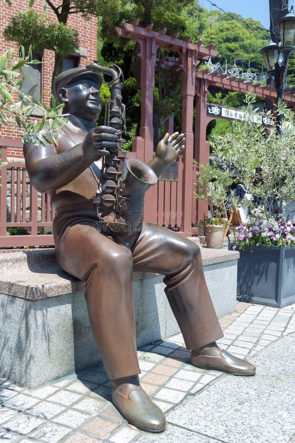 Statue de trompettiste devant la Chambre de girouette dans le secteur historique du secteur de Kitano à Kobe, Japon photographie stock libre de droits