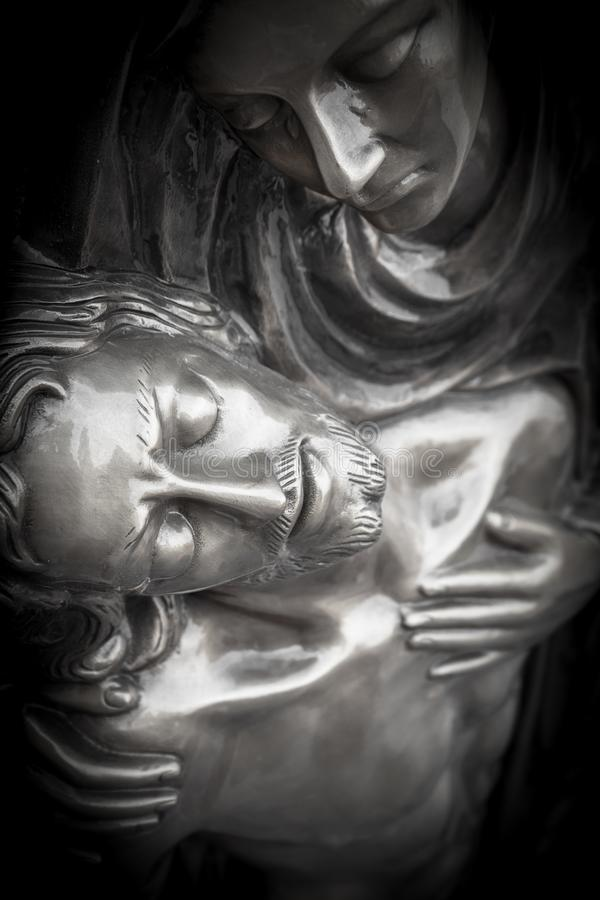 Statue of dead Jesus Christ being embraced by the Virgin Mary. Bronze Statue of dead Jesus Christ down from the cross, being embraced by the Virgin Mary. It can stock image
