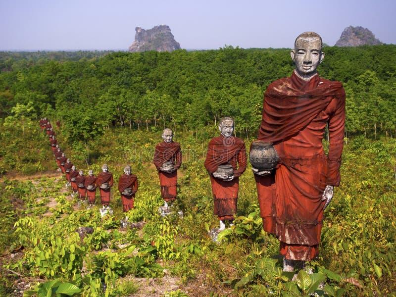 Statue dei monaci buddisti nella foresta, Mawlamyine, Myanmar immagine stock