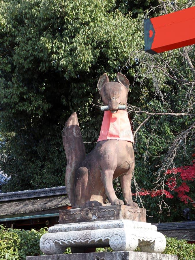 Statue delle volpi ai portoni principali del santuario al fondo della montagna al santuario shintoista di Fushimi Inari Taisha immagini stock libere da diritti