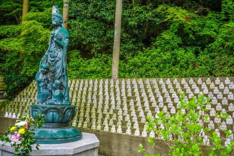 Statue depicting a Buddhist goddess keeping watch over many smaller Bhuddist statues. Munakata, Japan. Statue depicting a Buddhist goddess keeping watch over stock photo
