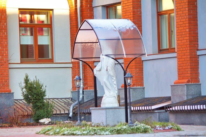 Statue der Jungfrau Mary Praying im Hof der Kirche lizenzfreie stockfotos