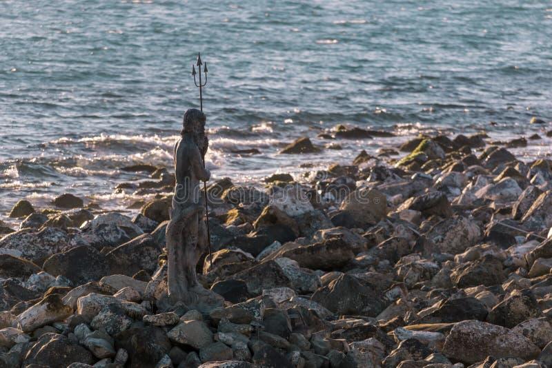 Statue des Gottes Neptun auf einer Klippe lizenzfreie stockfotos