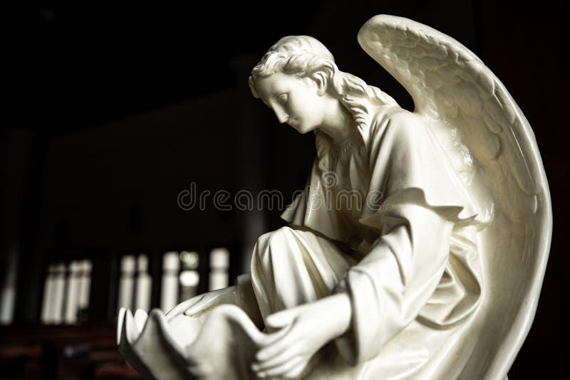 Statue di angelo davanti all'entrata alla chiesa cattolica fotografie stock libere da diritti