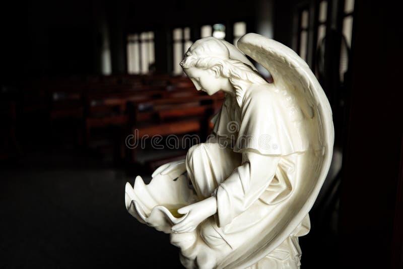 Statue di angelo davanti all'entrata alla chiesa cattolica fotografia stock libera da diritti