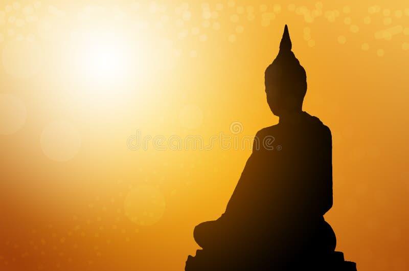 Statue di Buddha della siluetta sul fondo di tramonto della sfuocatura Concetto Buddha isolato su fondo vago arancio immagine stock libera da diritti