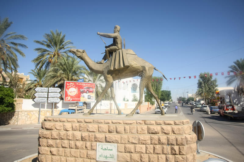 Statue in Douz. DOUZ, TUNISIA - SEPTEMBER 17, 2012 : A view of a racing came statue in the town of Douz, Tunisia. The city of Douz is famous for the camel racing royalty free stock photo