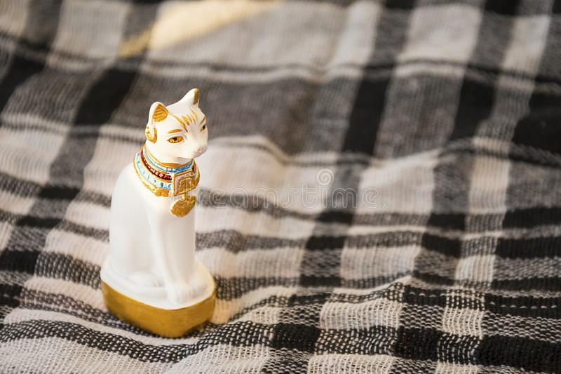 Statue du chat blanc de l'Egypte sur la surface couvrante vérifiée Élément égyptien traditionnel de cadeau image libre de droits