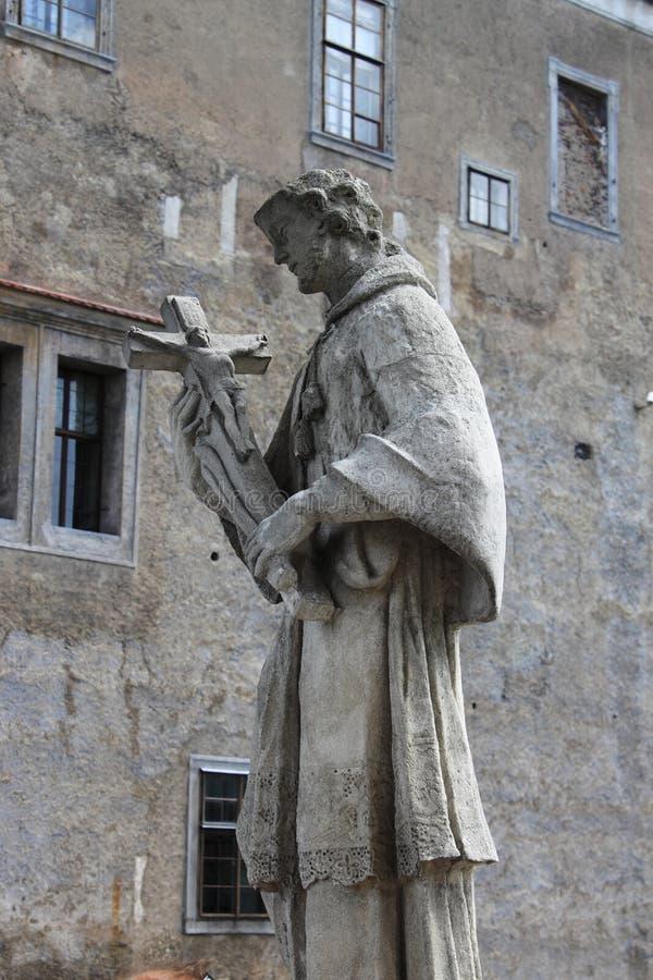 Statue eines Heiligen mit Kreuz stockbild