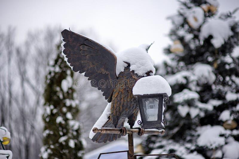 Statue eines Vogels mit offenen Flügeln auf einer Taschenlampe gegen ein backg stockfotos