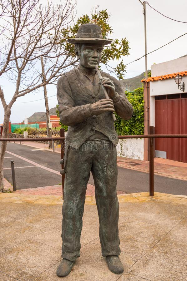 Statue en bronze d'un joueur de cannelure dans des vêtements canariens traditionnels photographie stock libre de droits