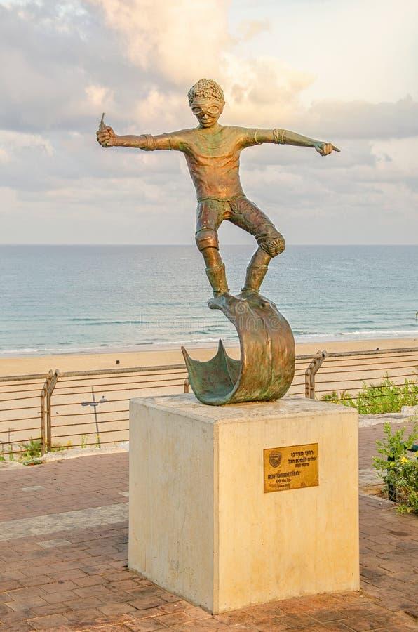 Statue en bronze d'un surfer inconnu au bord de la mer pendant l'heure de matin images stock