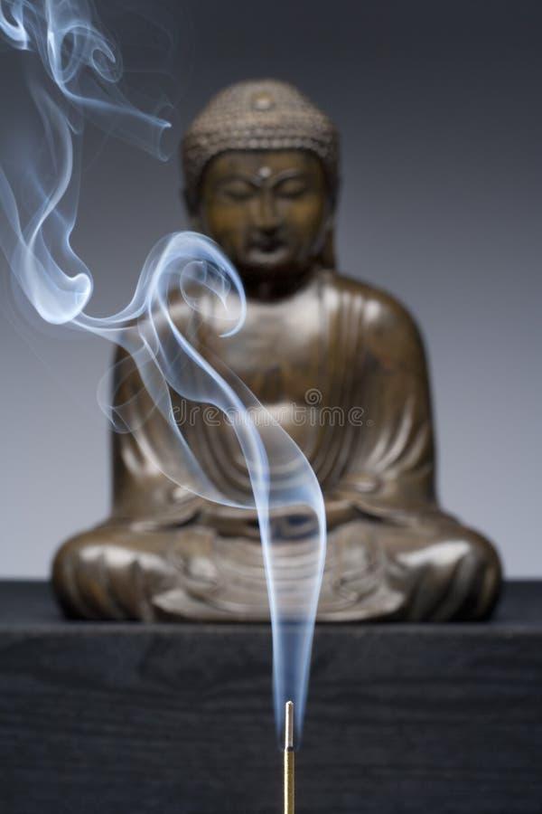 Statue en bronze de Bouddha avec de la fumée brûlante d'encens photographie stock libre de droits